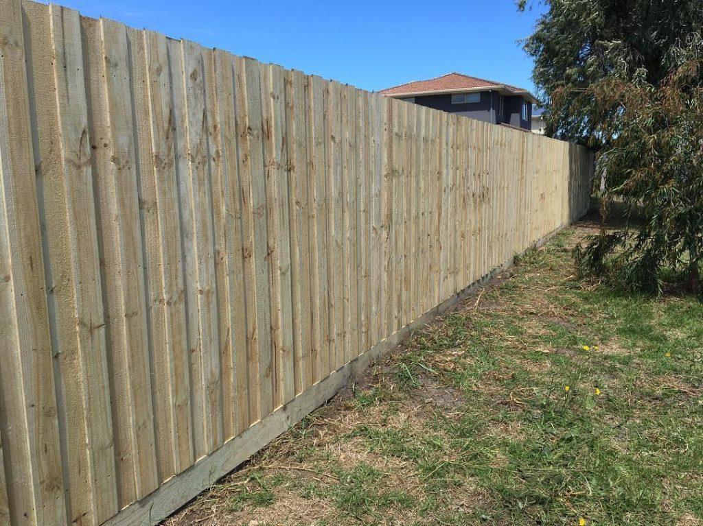 clôture avec des panneaux de bois brut